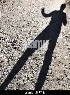 Shadow of a man with real long legs, waving. - Stock Photo