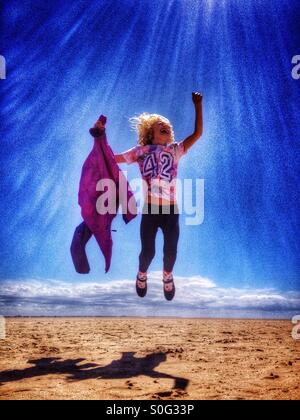 Young girl leaping for joy on the beach at Lytham St Annes - Stock Photo