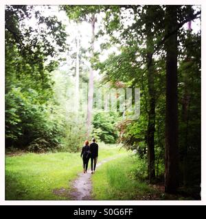 Boy and girl walking together in a forest on bare feet - Stock Photo