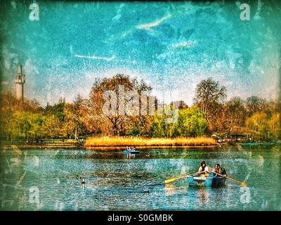 Couple rowing a boat on Regent's Park lake, City of Westminster, Central London, England, United Kingdom, Europe - Stock Photo
