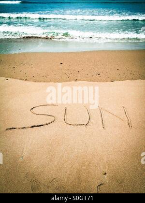 The word Sun written in the sand - Stock Photo