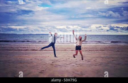 Boy and girl leaping on a beach - Stock Photo
