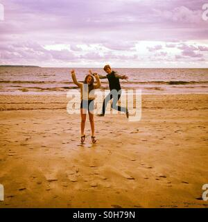 Boy and girl leaping on beach - Stock Photo