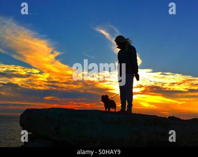 Sunset dog walks - Stock Photo