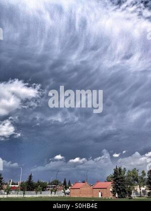 Large Cumulonibus storm cloud approaching a sports field, in Calgary, Alberta, Canada. July 2015. - Stock Photo