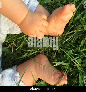 Baby's bare feet and hand on green grass - Stock Photo