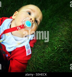 Baby boy with a pacifier is looking up - Stock Photo