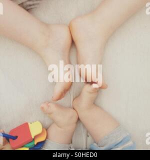 Baby's feet vs teenager's feet - Stock Photo