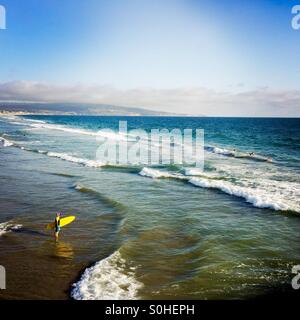 A surfer walks out to the surf. Manhattan Beach, California USA. - Stock Photo