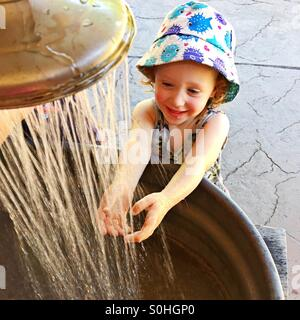 Happy toddler washing her hands - Stock Photo