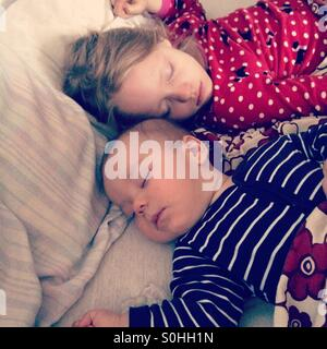 Two children sleeping peacefully together on parent's bed - Stock Photo