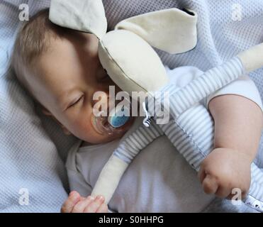 Baby boy sleeping with his bunny toy - Stock Photo