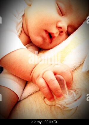 Sleeping baby boy holding his pacifier - Stock Photo