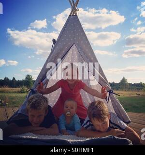 Four siblings together in teepee on hot summer day - Stock Photo