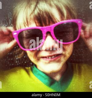 Four year old boy in oversized sunglasses - Stock Photo
