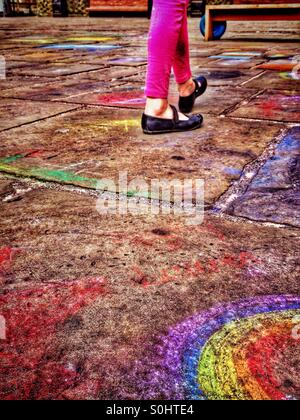 Young girl walking on pavement covered with child's chalk drawings - Stock Photo