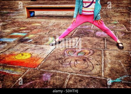 Young girl standing on pavement covered in chalk drawings - Stock Photo