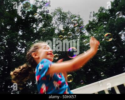 Little girl playing in bubbles - Stock Photo