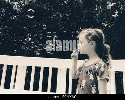 Black and white photo of little girl blowing bubbles outside - Stock Photo