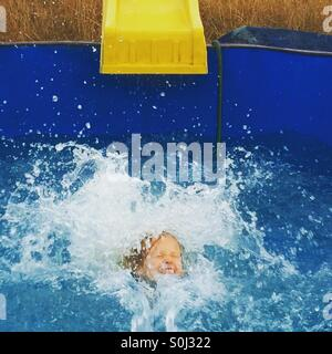 Girl slides down into the water from the diy water slide - Stock Photo