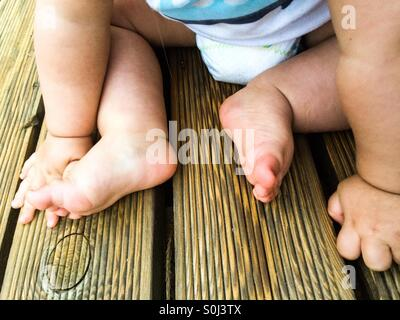 Baby's feet and hands on the wooden porch - Stock Photo