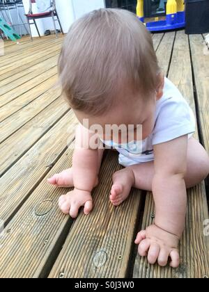 Baby boy sitting on the wooden porch touching the deck - Stock Photo