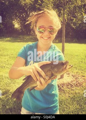 Young girl holding a Largemouth Bass she caught while fishing - Stock Photo