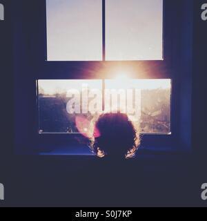 Boy watching sunrise through window - Stock Photo