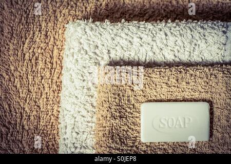 A bar of soap on top of a neatly folded pile of towels - Stock Photo