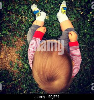 Photo from the top of a redhead baby boy sitting on the green grass at the end of a summer day, playing with grass - Stock Photo