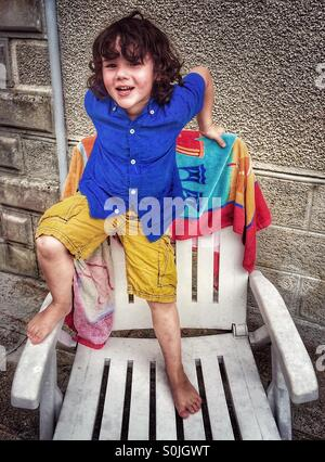 Four year old boy standing on patio chair - Stock Photo