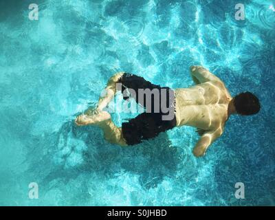 Teenager boy swimming underwater in outdoor swimming pool. - Stock Photo