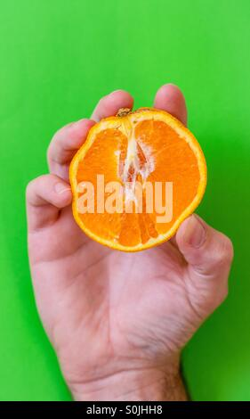 Mans hand holding a a sliced orange against a green background - Stock Photo