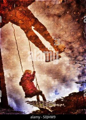 Reflections in muddy puddle of two girls on swings - Stock Photo