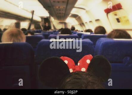 Inside of an airplane with passengers. Girl with Minnie Mouse ears headband in foreground. - Stock Photo