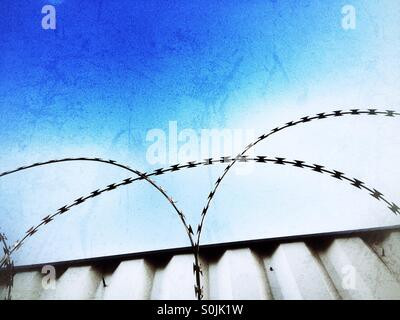 Razor wire fence on top of a metal gate set against a blue sky. - Stock Photo