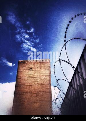 Razor wire fencing and stark building. - Stock Photo