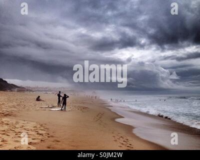 People surfing under a storm in the Atlantic Ocean, west coast of Portugal, with huge dark and gray clouds in the - Stock Photo