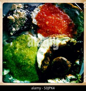 Black beans with three eggs with red, green and mole poblano sauces for breakfast in Cuetzalan, Sierra Madre, Puebla, - Stock Photo