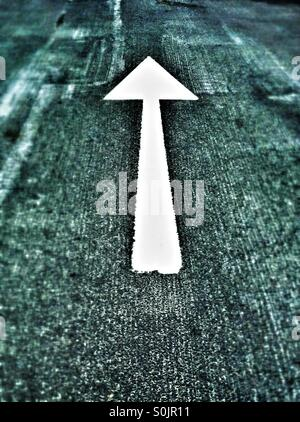 White arrow painted on road - Stock Photo