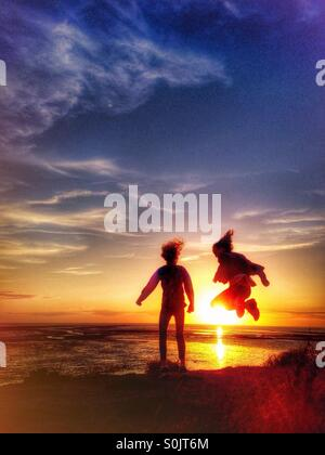 Two young girls having fun jumping in front of the setting sun - Stock Photo