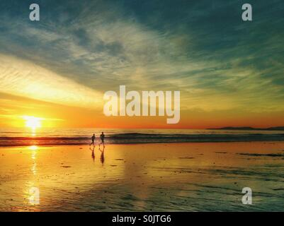 Beach Joggers At Sunset - Stock Photo