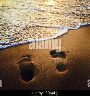 Footprints in the sand at the shoreline. Manhattan Beach, California USA. - Stock Photo