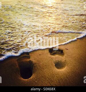 Waves rolling over Footprints in the sand at the shoreline. Manhattan Beach, California USA. - Stock Photo