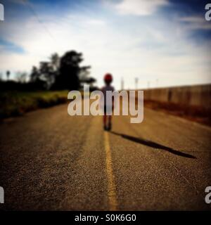 A 7 year old boy stands in the middle of a country road wearing his bicycle helmet. - Stock Photo
