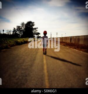 A 7 year old boy walks down the middle of a country road wearing his bicycle helmet. - Stock Photo