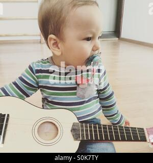 Baby boy playing guitar , looking to the side, sitting on a wooden floor in an empty room, with a pacifier in his - Stock Photo