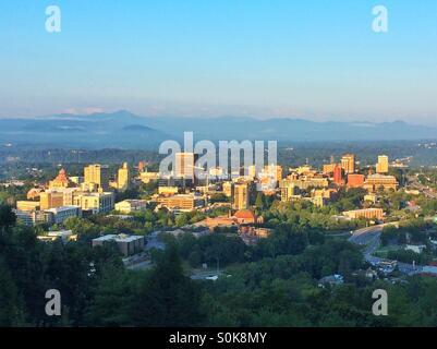 Sunrise illuminates the city of Asheville, North Carolina, nestled in the Blue Ridge Mountains. - Stock Photo