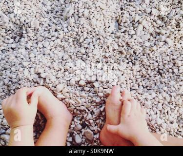 Small baby hands and foots on pebble beach - Stock Photo