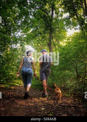 Couple walking dog in the woods - Stock Photo